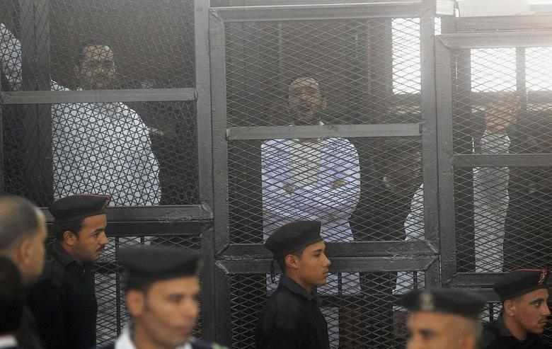 Political activists Ahmed Maher (R), Ahmed Douma (C) and Mohamed Adel, founder of 6 April movement, look on from behind bars in Abdeen court in Cairo, December 22, 2013. REUTERS/Stringer