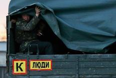 Военнослужащий, предположительно российский солдат, выглядывает из военного грузовика на украинской военной базе в Перевальном на полуострове Крым 5 марта 2014 года. Украинский офицер погиб от рук российского военнослужащего в Крыму, и покидающая полуостров украинская армия описала инцидент как убийство безоружного майора в общежитии после конфликта с занявшими Крым российскими военными. Российская полиция сообщила в тот же день, что в гарнизонном общежитии в том же районе прошлой ночью был застрелен хулиган. REUTERS/Thomas Peter