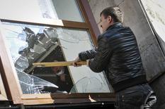 Пророссийский протестующий разбивает оконное стекло при штурме здания областной администрации в украинском Донецке 6 апреля 2014 года. Рубль достиг недельных минимумов на фоне нестабильности в восточных областях Украины, граничащих с Россией. REUTERS/Mikhail Maslovsky