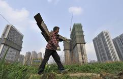 A garbage collector walks past residential and office buildings in construction, in Hefei, Anhui province, April 3, 2014. REUTERS/Stringer