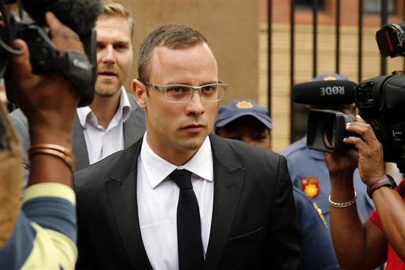 Oscar Pistorius leaves the court after his trial for the murder of his girlfriend, Reeva Steenkamp, was postponed at the North Gauteng High Court in Pretoria March 28, 2014. REUTERS/Siphiwe Sibeko