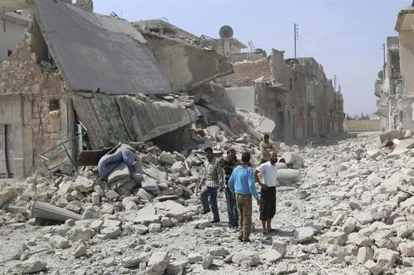 Residents walk over rubble after what activists said where explosive barrels thrown by forces loyal to Syria's President Bashar al-Assad in the Al-Sakhour neighbourhood of Aleppo April 5, 2014. REUTERS/Hosam Katan