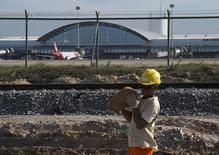A worker carries a rock at the site of the delayed construction of a new terminal at the Pinto Martins International Airport that is supposed to help with increased traffic during the 2014 World Cup, in Fortaleza January 21, 2014. REUTERS/Davi Pinheiro