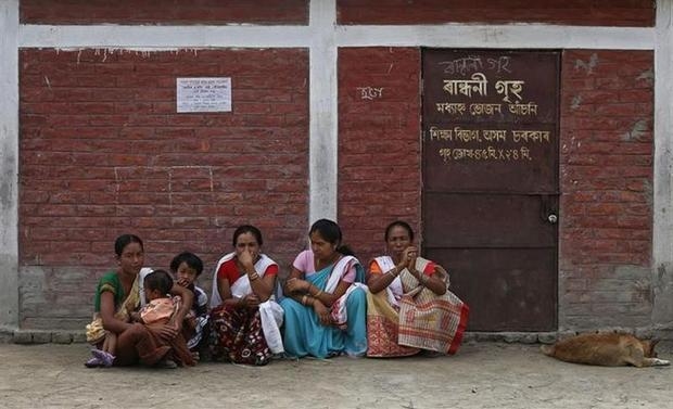 Women wait outside a polling station for their relatives after casting their vote in Majuli, a large river island in the Brahmaputra river, Jorhat district, in Assam April 7, 2014. REUTERS/Adnan Abidi