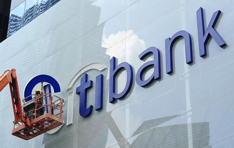 Construction workers install Citibank's neon sign on its Singapore main office at the central business district November 29, 2011. REUTERS/Harry Suhartono