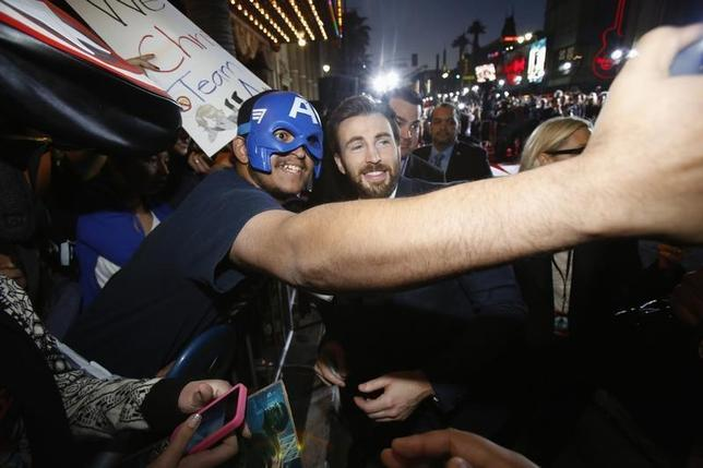 Cast member Chris Evans (R) poses with a fan at the premiere of ''Captain America: The Winter Soldier'' at El Capitan theatre in Hollywood, California March 13, 2014. REUTERS/Mario Anzuoni/Files