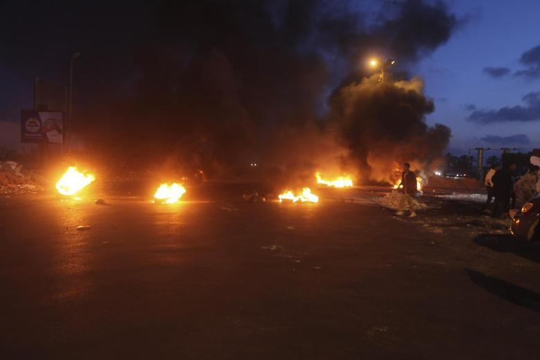 Burning obstacles are seen along a road leading to the airport in Tripoli, April 7, 2014. REUTERS/Hani Amara