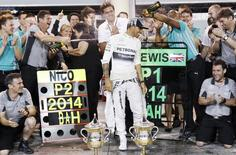 Mercedes Formula One driver Lewis Hamilton of Britain is sprayed with champagne by his team after his win in the Bahrain F1 Grand Prix at the Bahrain International Circuit (BIC) in Sakhir, south of Manama April 6, 2014. REUTERS/Thaier Al-Sudani
