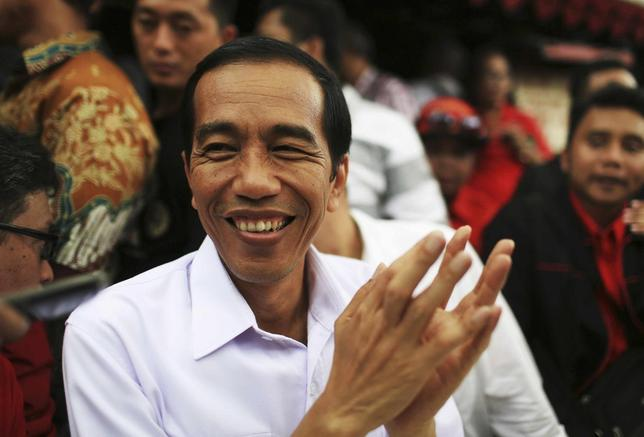 Jakarta governor and presidential candidate Joko Widodo, of the Indonesian Democratic Party of Struggle (PDI-P), reacts during a party campaign at Cengkareng soccer field in Jakarta March 16, 2014. REUTERS/Beawiharta
