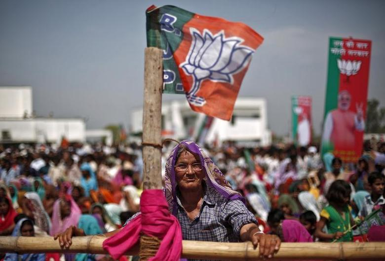 A supporter of Narendra Modi, prime ministerial candidate for the Bharatiya Janata Party (BJP) and Gujarat's chief minister, listens to his speech during a rally in Amroha, in Uttar Pradesh March 29, 2014. REUTERS/Adnan Abidi/Files