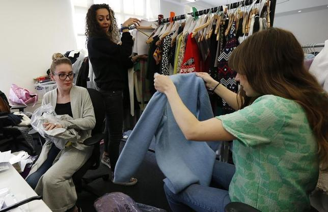 Knitwear buyers look at samples at the ASOS headquarters in London April 1, 2014. REUTERS/Suzanne Plunkett