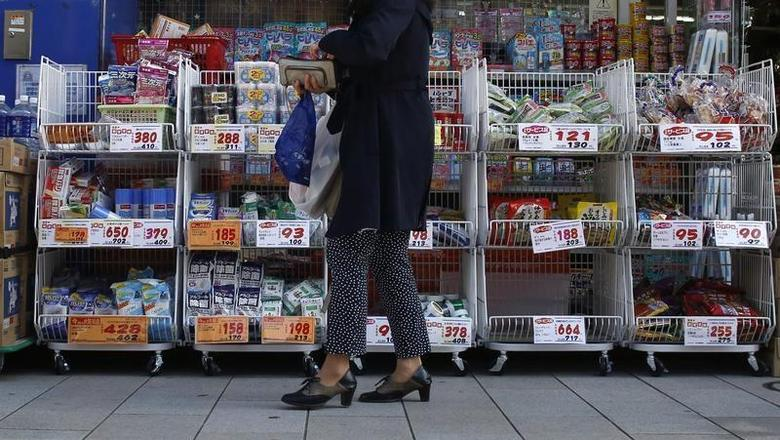 A woman stands outside a pharmacy in Tokyo April 7, 2014. REUTERS/Yuya Shino