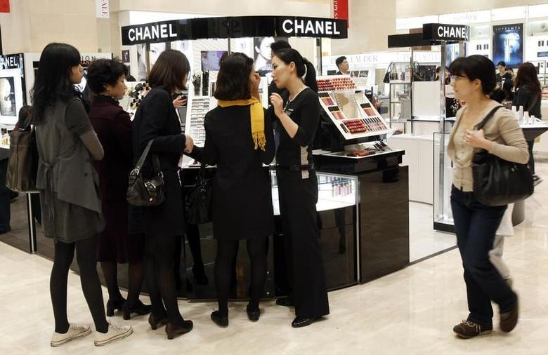 Customers choose cosmetics at a cosmetics counter at the Shinsegae department store in Seoul October 11, 2009. REUTERS/Jo Yong-Hak