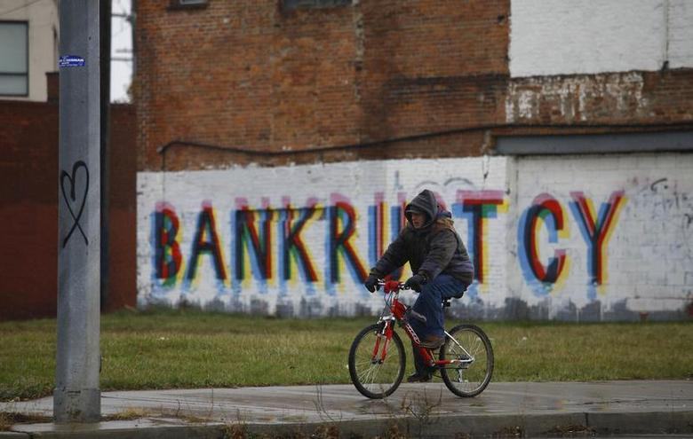 A man rides his bike past graffiti that reads ''Bankruptcy'' in Detroit, Michigan, December 3, 2013. REUTERS/Joshua Lott
