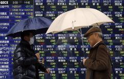 Pedestrians holding umbrellas walk past an electronic board showing stock prices outside a brokerage in Tokyo March 20, 2014. REUTERS/Yuya Shino
