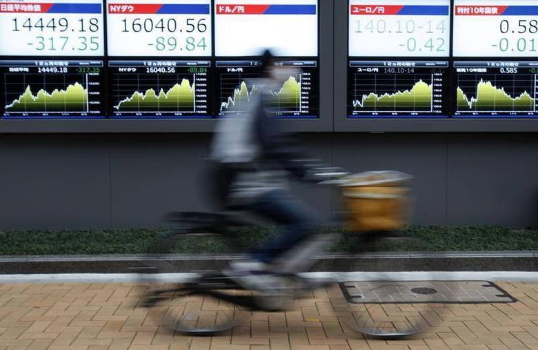 A man rides a bicycle past electronic boards showing the figures and graphs of recent fluctuations of Japan's Nikkei average (L), the U.S. NASDAQ average (2nd L), the Japanese yen's exchange rate against the U.S. dollar (C), Japanese yen's exchange rate against the euro (2nd R) and Japan's 10 year government bonds, outside a brokerage in Tokyo February 20, 2014. REUTERS/Yuya Shino