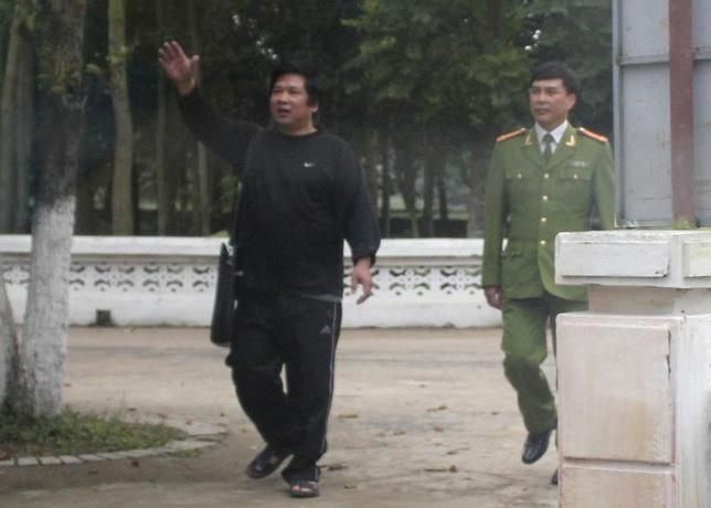 A policeman watches as Cu Huy Ha Vu (L) waves to his wife Duong Ha before their meeting at the Number 5 Prison in Thanh Hoa province, about 200 km (124 miles) south of Hanoi, in this picture taken from a car on February 24, 2012. REUTERS/Stringer