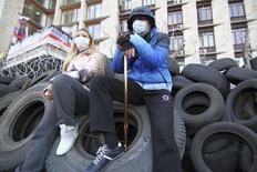 Пророссийские активисты сидят на автомобильных покрышках у здания обладминистрации в Донецке 7 апреля 2014 года. Российские фондовые индексы продолжили снижение в начале торгов вторника в условиях коррекции на Уолл-стрит и эскалации напряженности в Донецке и некоторых других городах Восточной Украины. REUTERS/Stringer