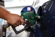 Работник АЗС компании PDVSA в Каракасе заправляет автомобиль 16 декабря 2013 года. Цены на нефть растут в связи с ситуацией на Украине, но подъем сдерживается предстоящим возобновлением отгрузок нефти из ливийских портов. REUTERS/Carlos Garcia Rawlins