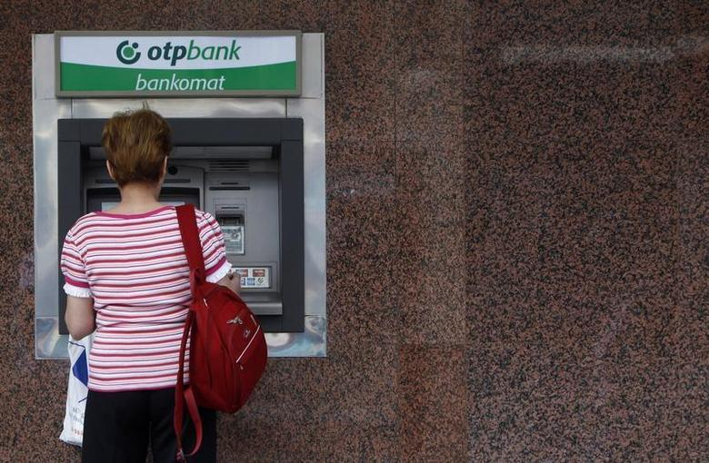 A woman withdraws money from an ATM at an OTP bank in Budapest June 7, 2010. REUTERS/Laszlo Balogh