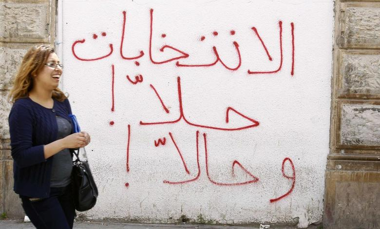A woman walks near a wall with graffiti which reads ''The elections now now'' in central Tunis April 7, 2014. REUTERS/Zoubeir Souissi