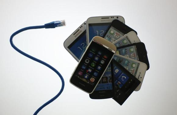 An illustration picture shows a network cable next to a pack of smartphones in Berlin, June 7, 2013. REUTERS/Pawel Kopczynski