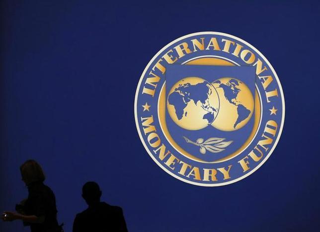 4月8日、IMFは、2014年の世界経済の成長率予想を3.6%とし、前回予想から引き下げた。写真はIMFのロゴマークと人影。都内で2012年10月撮影(2014年 ロイター/Kim Kyung-Hoon)