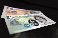 Unos billetes de 5 y 10 libras esterlinas en el Banco de Inglaterra en Londres, sep 10 2013. La ayuda para el desarrollo que envían países ricos a algunas de las naciones más pobres del mundo aumentó a un récord el año pasado, pero las contribuciones de Europa quedaron rezagadas en momentos en que la región intenta salir de la recesión. REUTERS/Chris Ratcliffe/pool