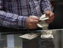 A man counts U.S. dollars at a currency exchange office in central Tripoli March 30, 2014. REUTERS/Ismail Zitouny