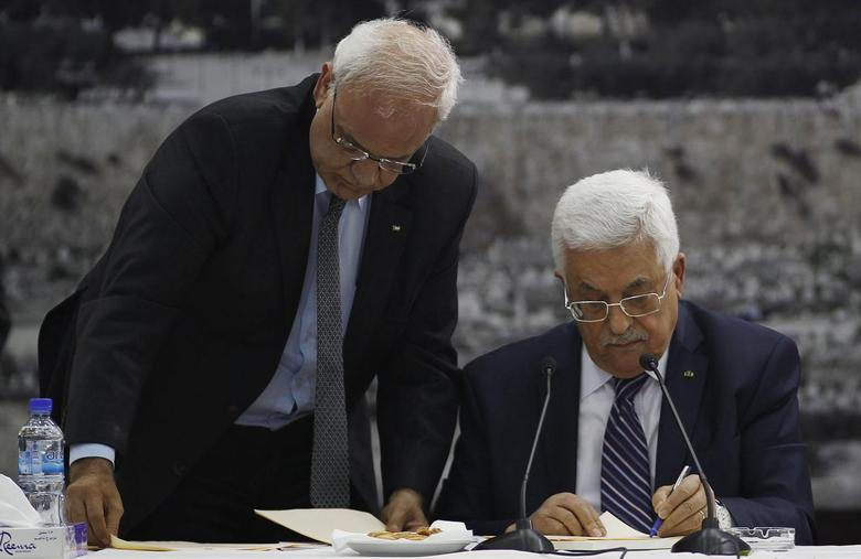 Palestinian chief negotiator Saeb Erekat (L) helps Palestinian President Mahmoud Abbas as he signs international conventions during a meeting with Palestinian leadership in the West Bank City of Ramallah April 1, 2014. REUTERS/Mohamad Torokman
