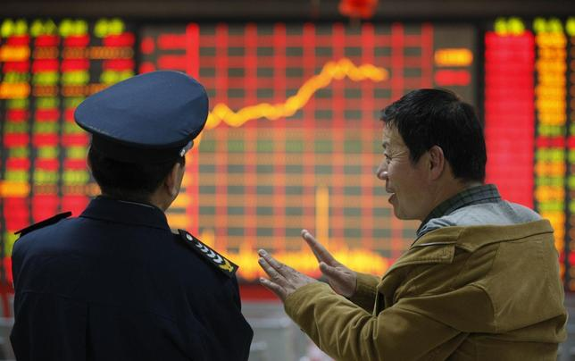 An investor (R) talks to a security guard in front of an electronic board showing stock information at a brokerage house in Huaibei, Anhui province April 8, 2014. REUTERS/Stringer
