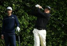 U.S. golfer Phil Mickelson (R) tees off on the fifth hole as compatript Dustin Johnson watches during a practice round ahead of the Masters golf tournament at the Augusta National Golf Club in Augusta, Georgia April 8, 2014. REUTERS/Mike Blake