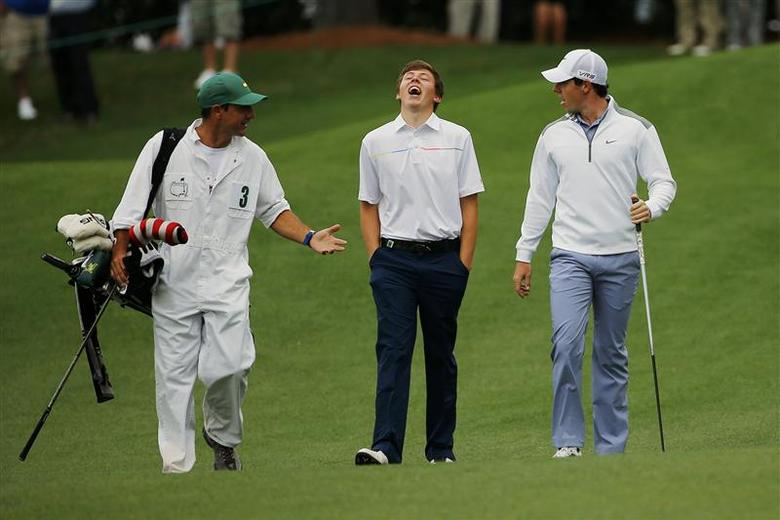 Britain's amateur Matthew Fitzpatrick (C) and Northern Ireland's Rory McIlroy (R) walk up the ninth fairway during a practice round ahead of the 2014 Masters golf tournament at the Augusta National Golf Club in Augusta, Georgia April 8, 2014. REUTERS/Brian Snyder