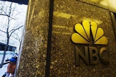 A man walks past an NBC logo outside Rockefeller Center in New York April 30, 2013. REUTERS/Lucas Jackson