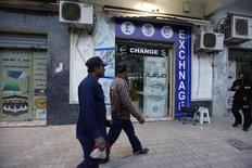 Пешеходы проходят мимо пункта обмена валюты в центре Триполи 30 марта 2014 года. Курс доллара близок к трехнедельному минимуму к корзине основных валют на фоне укрепления иены и евро. REUTERS/Ismail Zitouny