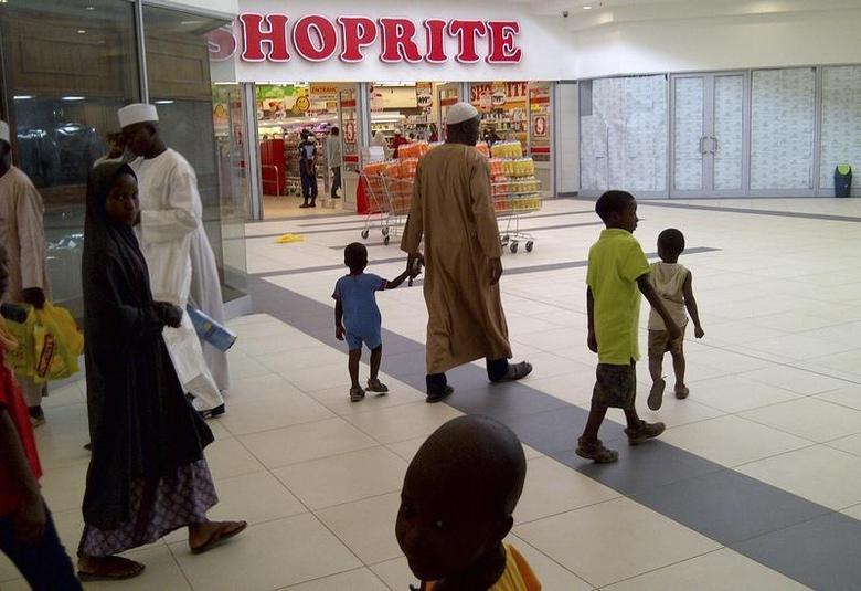 A Nigerian family walks past a newly-opened Shoprite supermarket in Nigeria's northern city of Kano April 2, 2014. REUTERS/Pascal Fletcher