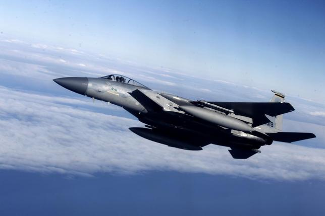 A U.S. Air Force F-15 fighter is seen as it escorts a Lithuania's Air Force C-27J plane during a joint NATO military exercise in Siauliai April 1, 2014. REUTERS/Ints Kalnins