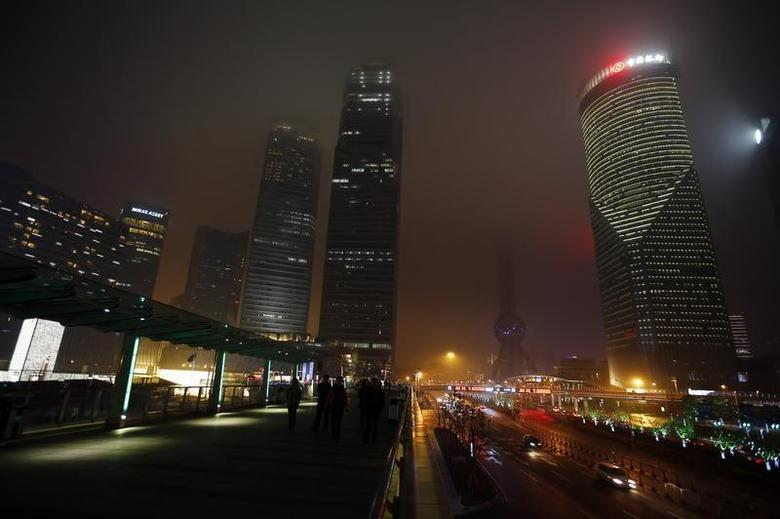 People walk at the financial district of Pudong during Earth Hour in Shanghai March 29, 2014. REUTERS/Carlos Barria
