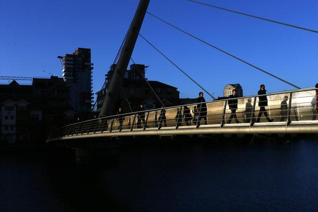 Workers walk across a footbridge towards the Canary Wharf business district in London February 26, 2014. REUTERS/Eddie Keogh