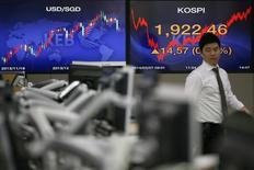 Мужчина проходит мимо экранов с котировками в банке в Сеуле 7 февраля 2014 года. Азиатские фондовые рынки, кроме Японии, выросли в среду благодаря повышенному спросу на отдельные компании. REUTERS/Kim Hong-Ji