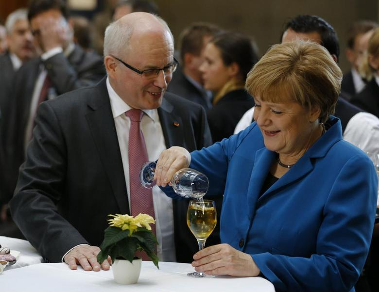 German Chancellor Angela Merkel, leader of the Christian Democratic Union (CDU), speaks with CDU faction leader Volker Kauder after signing a coalition treaty in Berlin, December 16, 2013. REUTERS/Thomas Peter