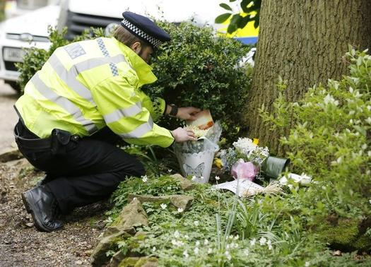 A police officer arranges flowers left by members of the public at the house of Peaches Geldof the day after she was found dead at her home near Wrotham, southern England April 8, 2014. REUTERS/Olivia Harris