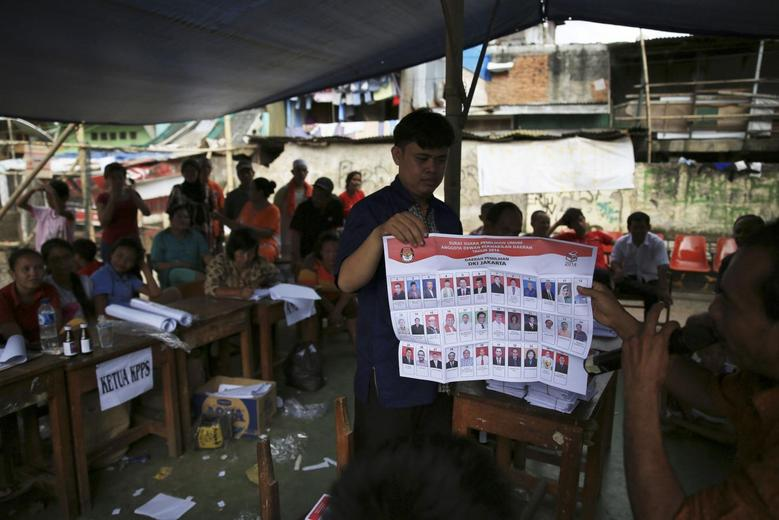 Electoral officials check ballot papers during vote counting at a polling station in Jakarta April 9, 2014. REUTERS/Beawiharta