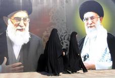 Жительницы Ирака проходят мимо изображений духовного лидера Ирана аятоллы Али Хаменеи в Багдаде 12 февраля 2014 года. Иран должен продолжить переговоры с мировыми державами для того, чтобы положить конец давнему конфликту вокруг ядерной программы Тегерана, при этом не упуская полученной благодаря ей выгоды, заявил аятолла. REUTERS/Ahmed Saad