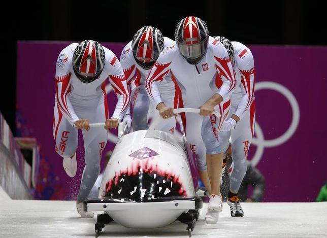 Poland's pilot Dawid Kupczyk (front R), Daniel Zalewski, Michal Kasperowicz and Pawel Mroz start a heat during the four-man bobsleigh event at the Sochi 2014 Winter Olympics, at the Sanki Sliding Center in Rosa Khutor February 22, 2014. REUTERS/Arnd Wiegmann