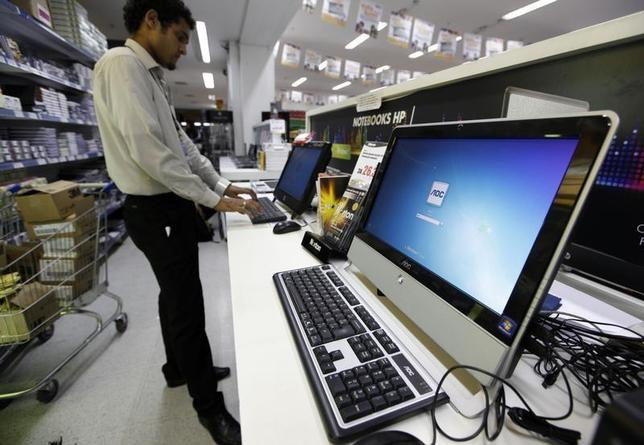 A Brazilian vendor types on a computer at a supermarket in Sao Paulo March 3, 2011. REUTERS/Nacho Doce/Files