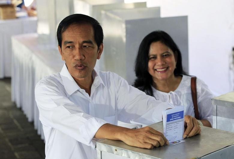 Jakarta governor and presidential candidate from the Indonesian Democratic Party-Struggle (PDI-P) party, Joko Widodo, and his wife Iriana cast their ballot papers during voting in the parliamentary elections in Jakarta April 9, 2014. REUTERS/Beawiharta