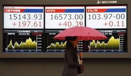 Женщина проходит мимо табло, отображающих финансовую информацию, в Токио 3 апреля 2014 года. Азиатские фондовые рынки, кроме Японии, выросли в четверг за счет местных новостей. REUTERS/Toru Hanai