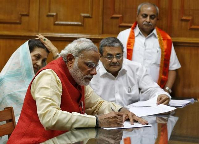 Hindu nationalist Narendra Modi, prime ministerial candidate for India's main opposition Bharatiya Janata Party (BJP), signs his nomination papers for the general elections in Vadodara, Gujarat April 9, 2014. REUTERS/Amit Dave