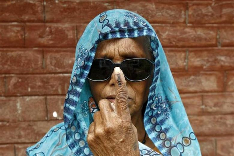 A woman shows her ink-marked finger after casting her vote at Makum village in Tinsukia district of Assam April 7, 2014. REUTERS/Rupak De Chowdhuri